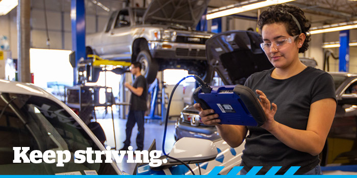 Student mechanic with 'Keep Striving' text overlaid
