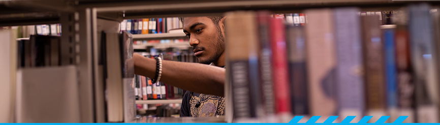 Student in the library stacks at Desert Vista campus library
