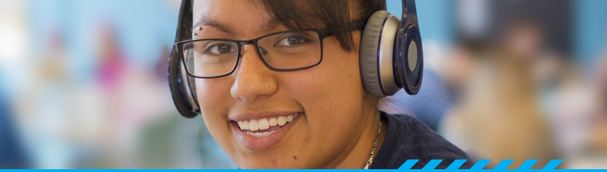 Pima Community College student wearing headphones and smiling